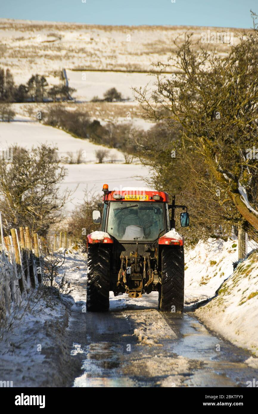 Pontypridd, Wales - December 2017: Farm tractor driving down a snow covered country lane in winter Stock Photo