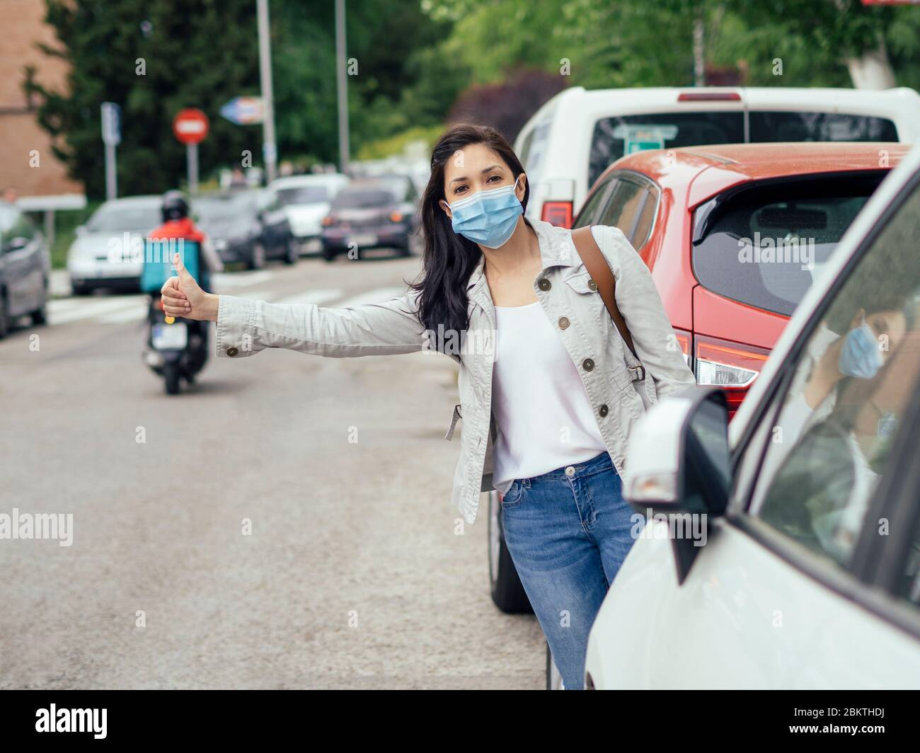 Woman hitchhiking. She is wearing a protective mask for the prevention of a virus. Coronavirus concept. Stock Photo