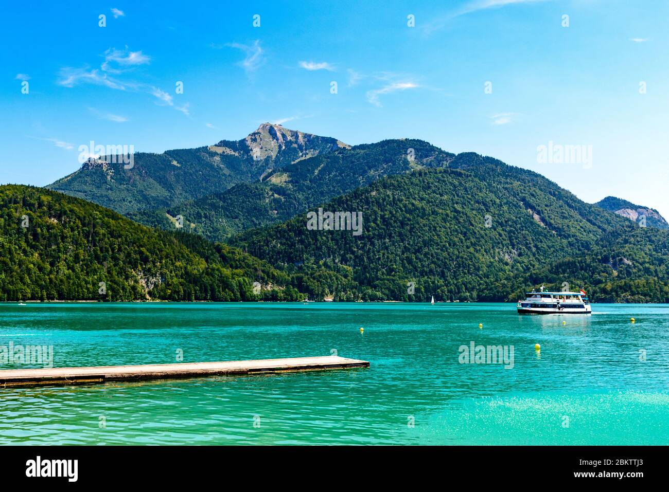 Beautiful view on Wolfgangsee lake by in St Sankt Gilgen with alps mountains, boats, Sailboats, blue sky, clouds, Schafberg mountain, ship.  Salzkamme Stock Photo