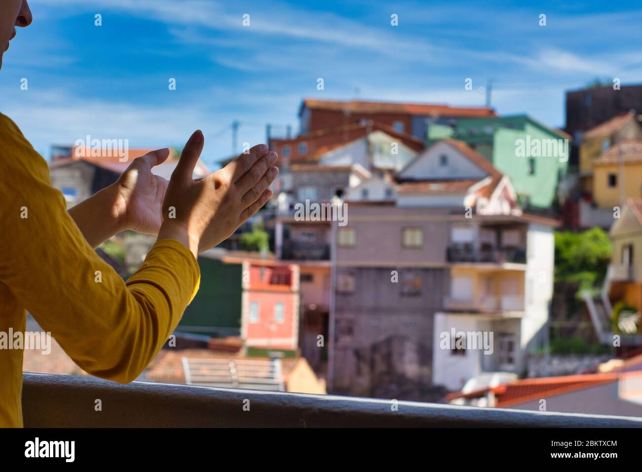 Young woman clapping her hands on the balcony to showi gratitude to all healthcare workers during the coronavirus outbreak. Lots of colorful houses. Stock Photo