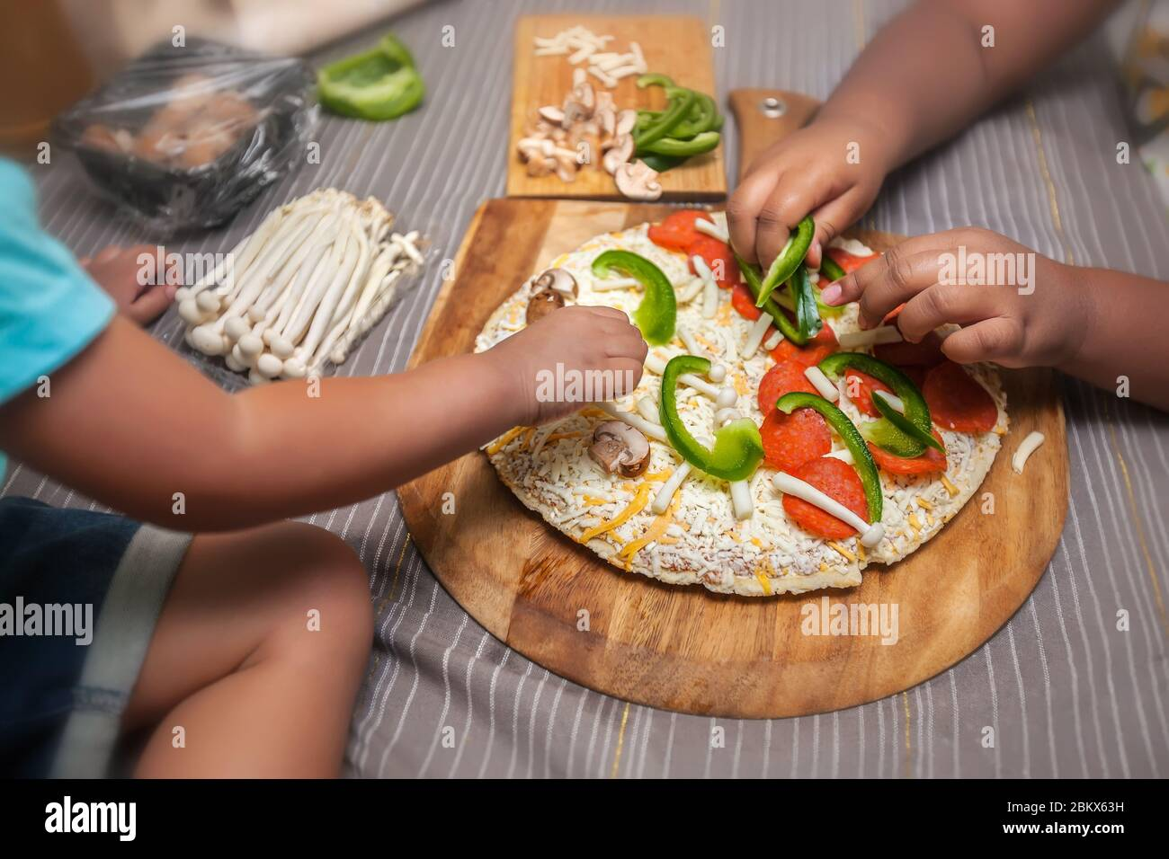 Children adding fresh toppings to a frozen cheese pizza on a wooden pizza peel. Stock Photo