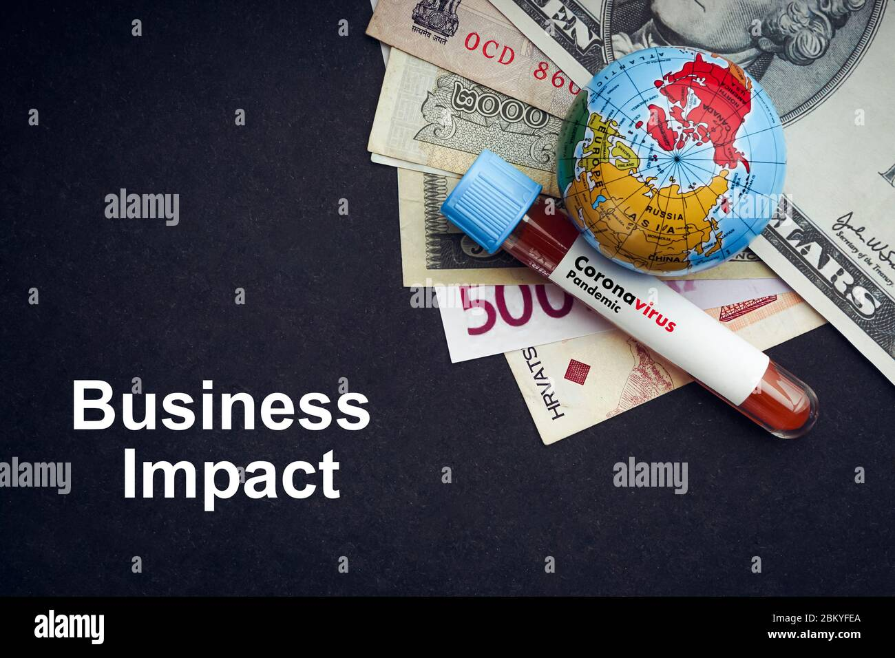 CORONAVIRUS BUSINESS IMPACT text with currency banknotes, world globe and blood test vacuum tube on black background. Covid-19 or Coronavirus Concept Stock Photo