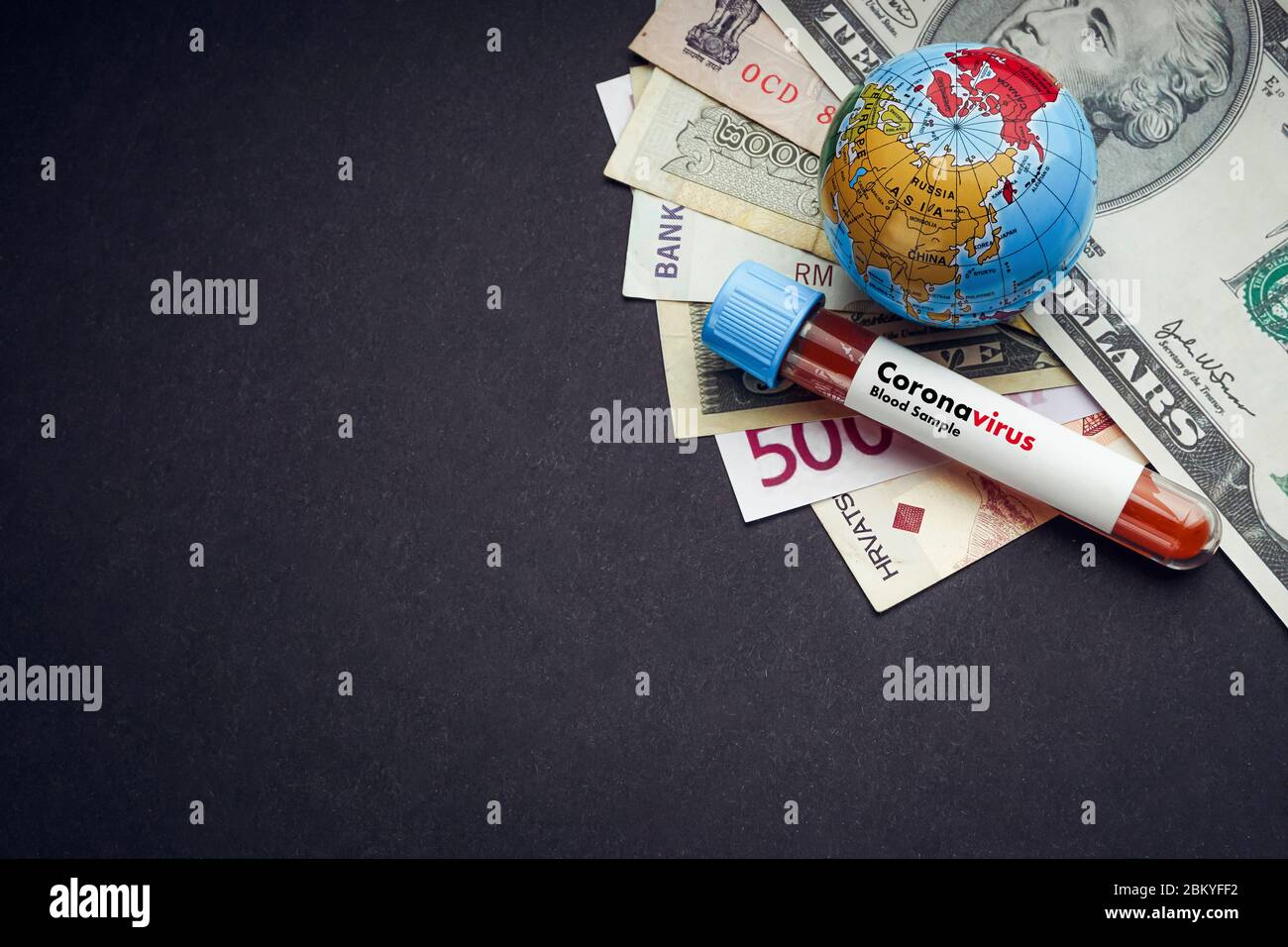 CORONAVIRUS text with currency banknotes, world globe and blood test vacuum tube on black background. Covid-19 or Coronavirus Concept. Copy space Stock Photo