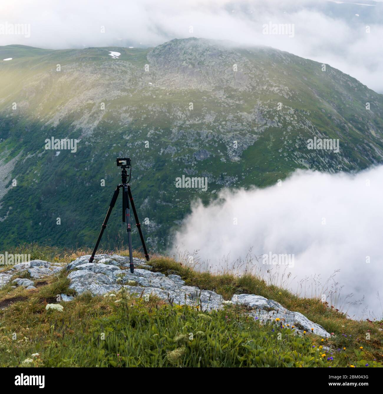 The mountain passes and the Alps are a paradise for photographers. Tripod. View of the clouds and the first rays of sun from the road of Grimsel Pass Stock Photo