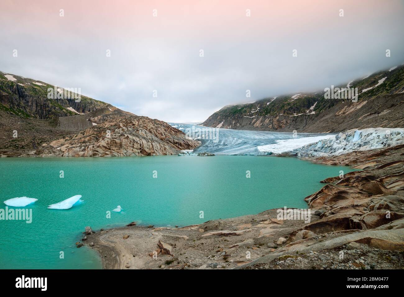 mighty glacier at sunrise in the swiss alps. The Rhone glacier and its glacier tongue lake on the street of the Furka pass at an altitude of 2200m Stock Photo