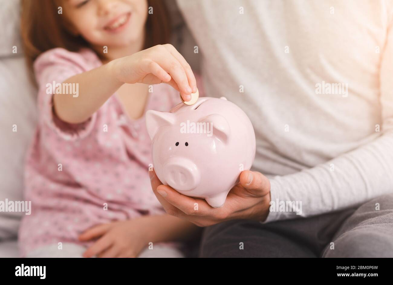 Cropped of girl putting money in piggy bank Stock Photo