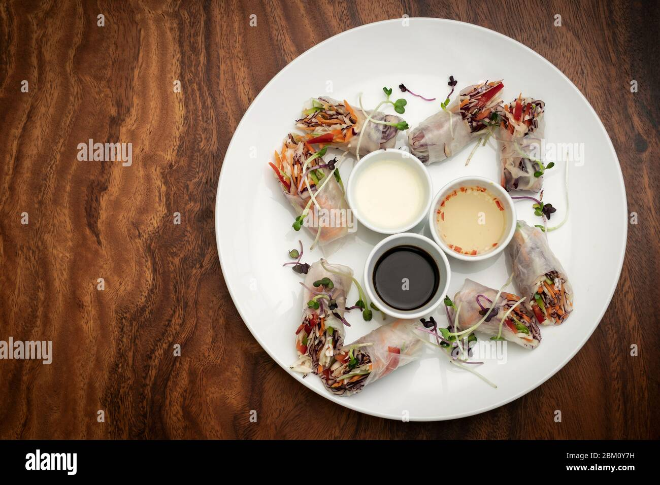 asian fresh vegetable vegan spring rolls with sauces on wood restaurant table in hanoi vietnam Stock Photo