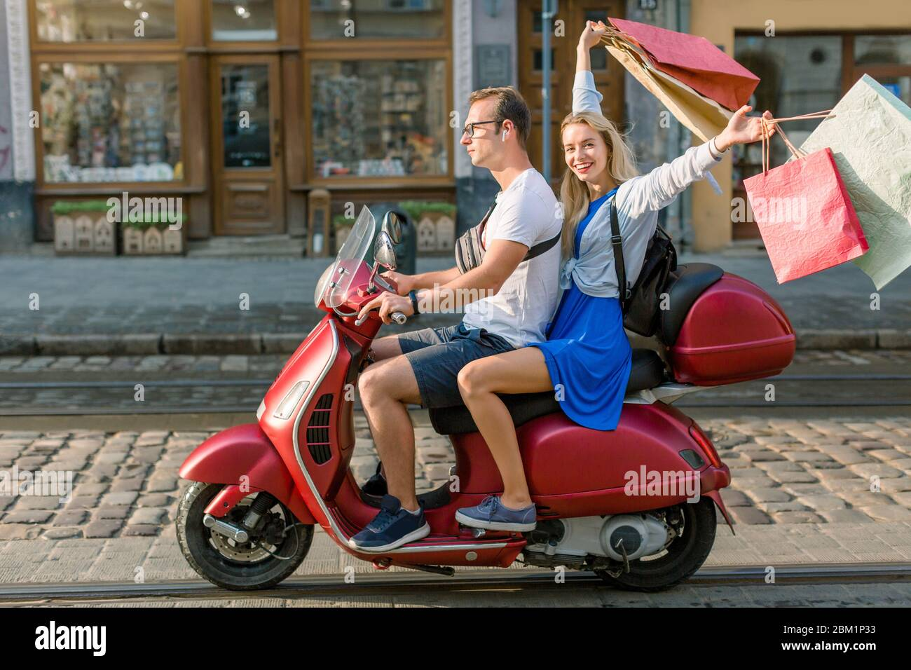 Summertime, urban lifestyle. Trendy young couple having fun on red vintage scooter in the streets, pretty smiling blond woman has her shopping bags Stock Photo