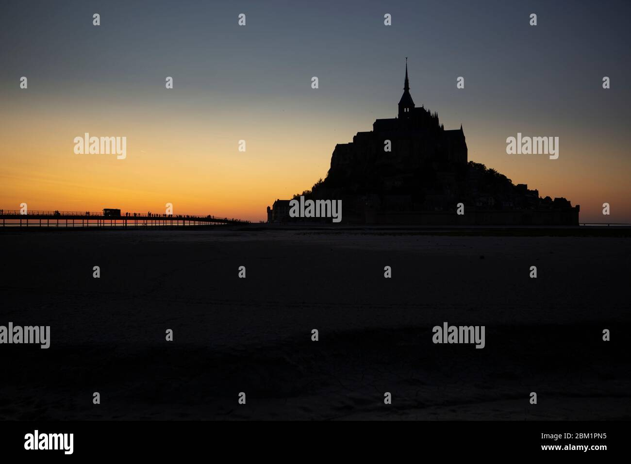 Sunset silhouette of Le Mont Saint Michel, France. People are walking on the bridge to visit the monastery. Stock Photo