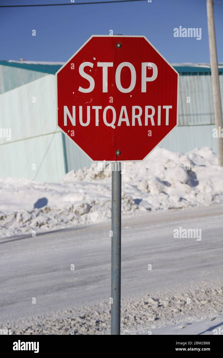Red stop sign in English and Inuinnaqtun in the community of ...