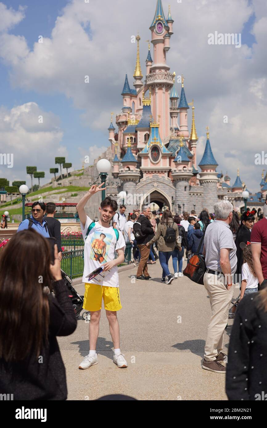 Girl is taking a picture of a young man in park with fairy tail castle in background and in the middle of crowd of visitors. Paris France, 29. May 201 Stock Photo