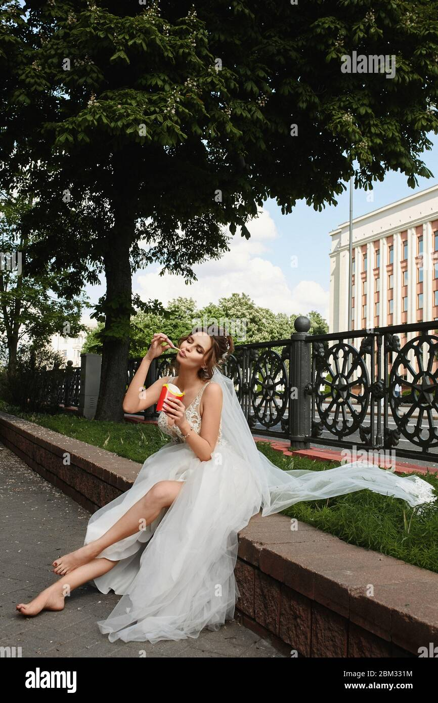 https://c8.alamy.com/comp/2BM331M/happy-young-bride-in-wedding-dress-sits-in-city-park-with-bare-feet-and-eating-french-fries-concept-of-wedding-fashion-2BM331M.jpg