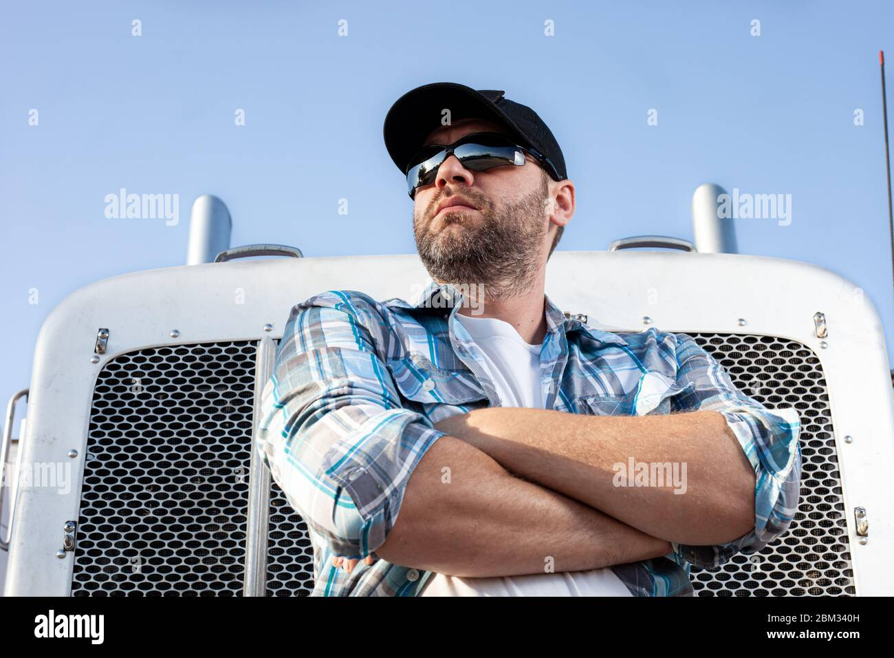 Confident semi truck driver wearing plaid shirt and black baseball cap  stands with arms crossed in front of big rig. Stock Photo