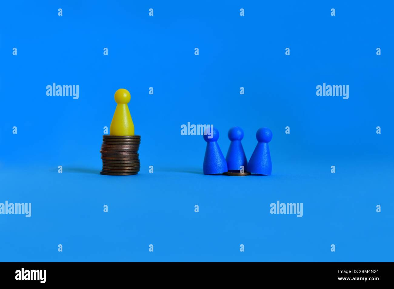 Pawns standing on piles of different sizes of coins. Income and economic inequality concept. Stock Photo