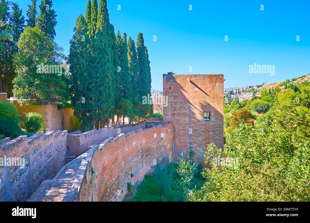 The medieval brick wall and Tower of Captive of Alhambra fortress is surrounded by lush greenery, Granada, Spain Stock Photo