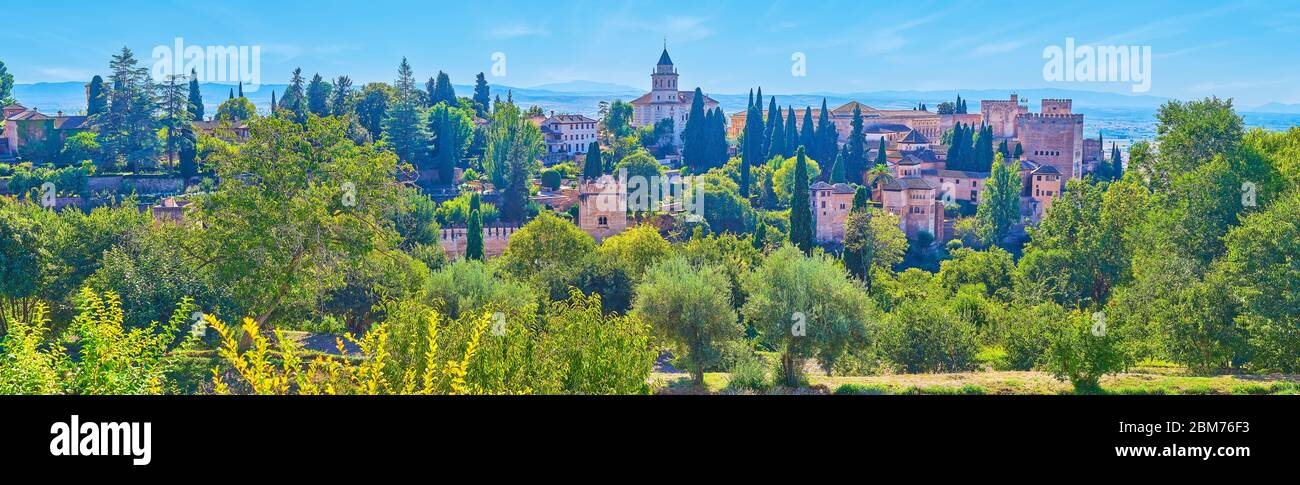 Observe the panorama of Alhambra fortress with towers, ramparts, Alcazaba and Santa Maria Church, surrounded by lush greenery, Granada, Spain Stock Photo
