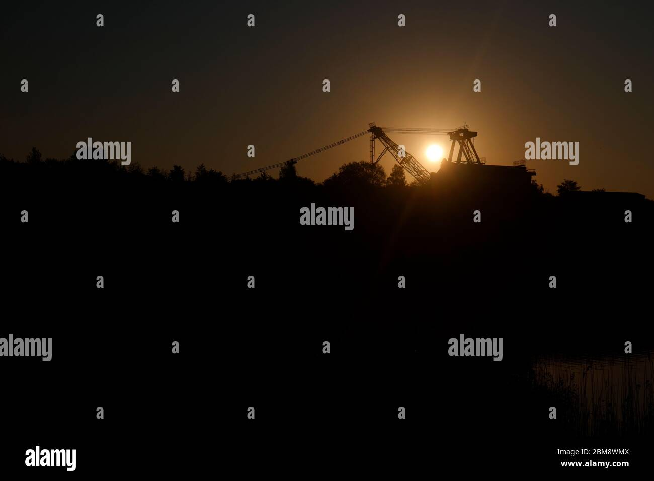 Sunrise behind a preserved walking dragline at RSPB St Aidan's in Swillington,Leeds,UK Stock Photo