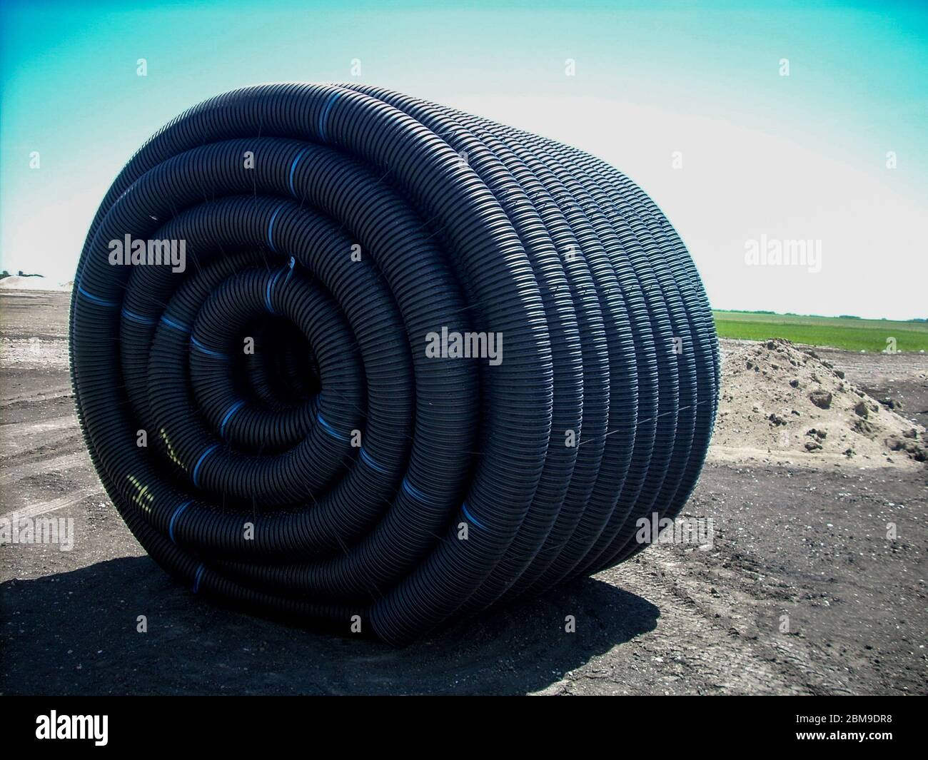 Spool of HDPE drainage tile sitting in agricultural field Stock Photo