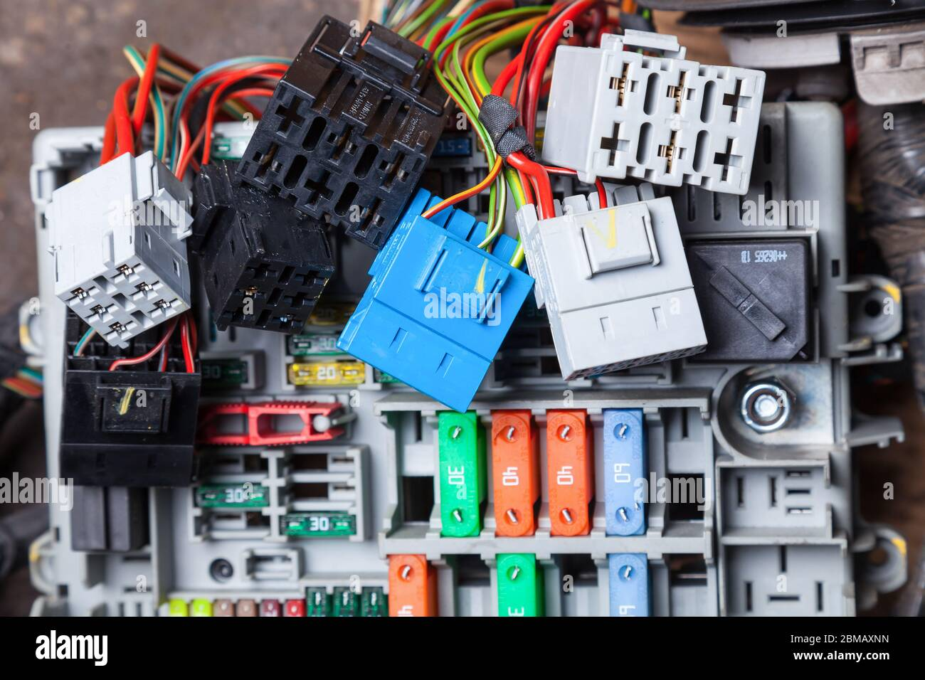 Multi-colored electrical wires - yellow green and red with connectors in  gray blue and black and with fuse boxes on the panel with holders for car  rep Stock Photo - AlamyAlamy