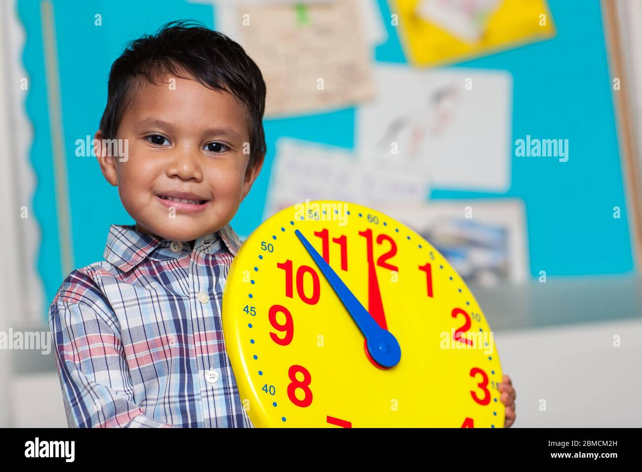 Young boy with a preppy shirt, holding a big analog clock with a colorful bulleting board in the background. Stock Photo
