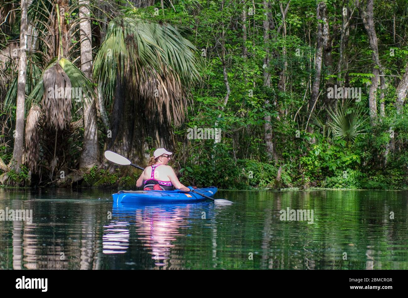 An active senior woman kayaks on the Silver River in Silver Springs State Park, Florida Stock Photo