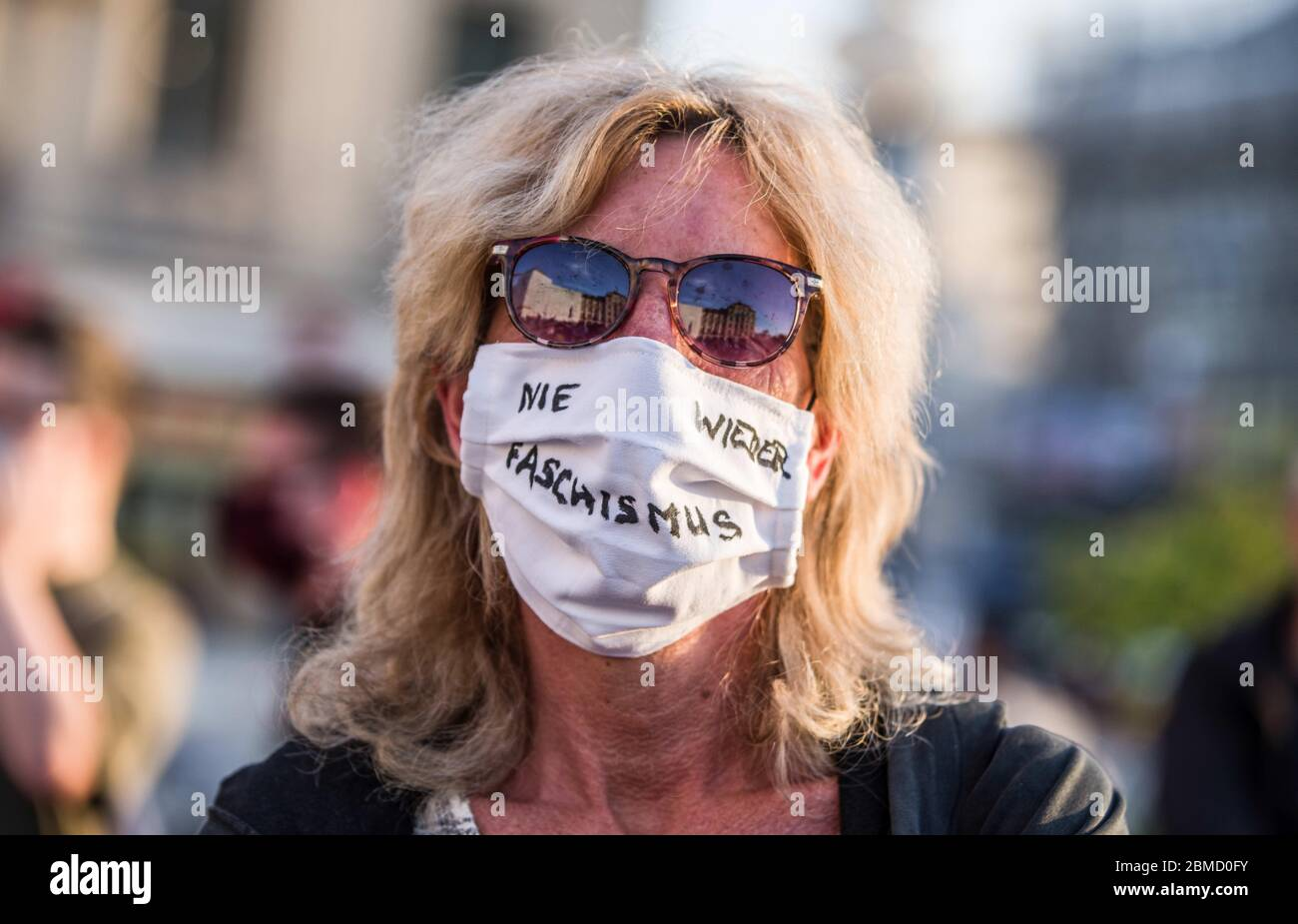 May 8, 2020, Munich, Bavaria, Germany: A demonstrator against neonazis at Munich's Stachus has ''nie wieder Faschismus'' (Never Again to Fascism) written on her mask. Also known as the Tag der Befreiung, neonazis from III. Weg led by multi-activist Roland Wuttke and convicted terrorist Karl Heinz Statzberger took advantage of the relaxing of anti-Coronavirus measures to demonstrate at Munich's Stachus. Due to today being the 75th anniversary of the unconditional surrender of the German military in WWII, this action is being seen as a provocation. Credit: ZUMA Press, Inc./Alamy Live News Stock Photo
