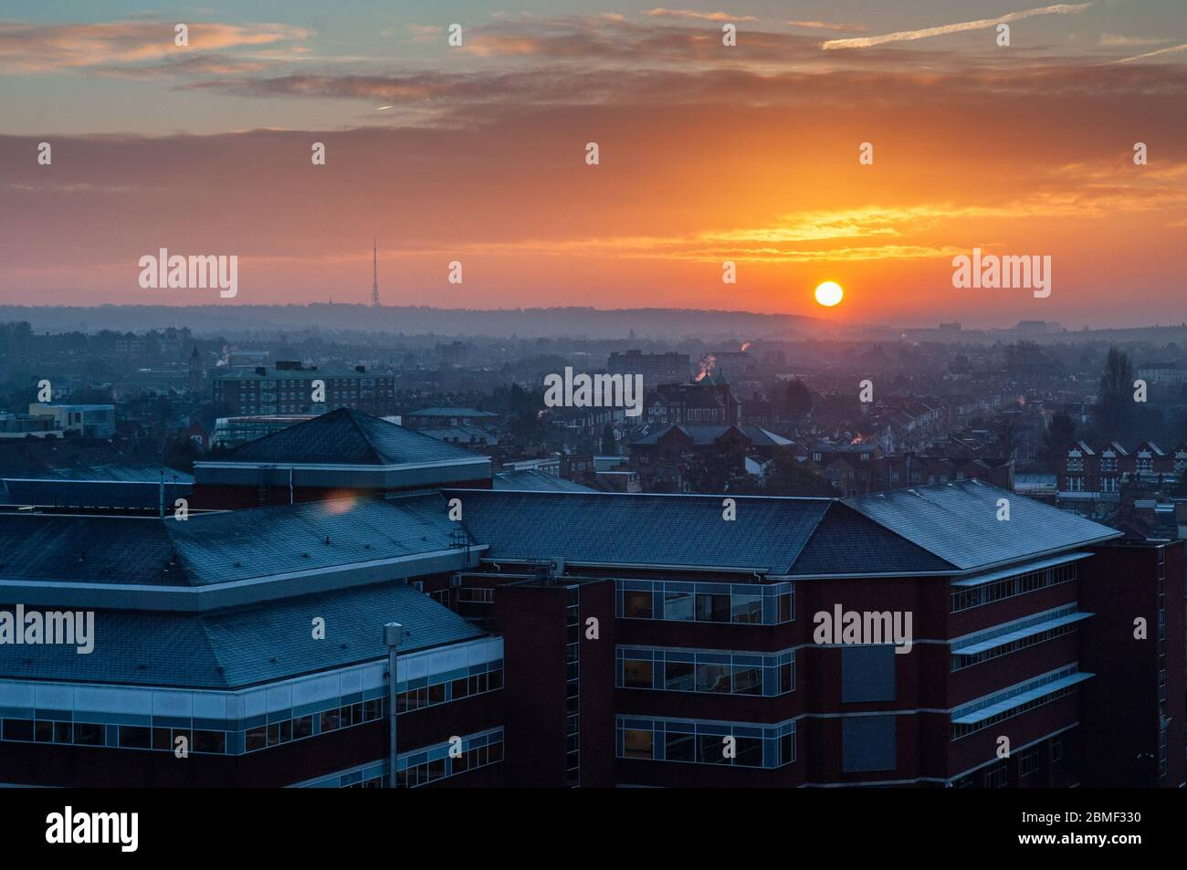 London, England, UK - February 8, 2013: The sun rises over St George's Hospital and the suburban housing of Tooting in South London. Stock Photo