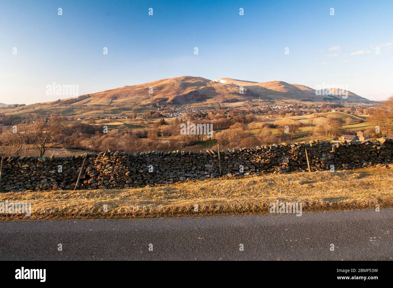 The snow-capped Howgill Fells hills rise bind the town of Sedbergh in the Yorkshire Dales National Park. Stock Photo