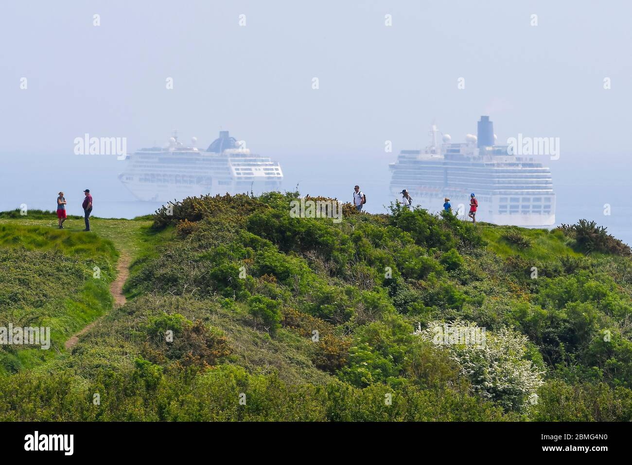 Weymouth, Dorset, UK.  9th May 2020.  UK Weather:   Walkers on the cliff top on the South West Coast Path with a view of the five cruise ships anchored in the bay off the coast of the seaside resort of Weymouth in Dorset on a hot sunny day due to the cruising industry shutting down during the coronavirus lockdown.  There are four P&O ships which are The Oceana, Aurora, Arcadia and Ventura and one Cunard ship the liner Queen Mary 2.  (Oceana and Arcadia pictured) Picture Credit: Graham Hunt/Alamy Live News Stock Photo