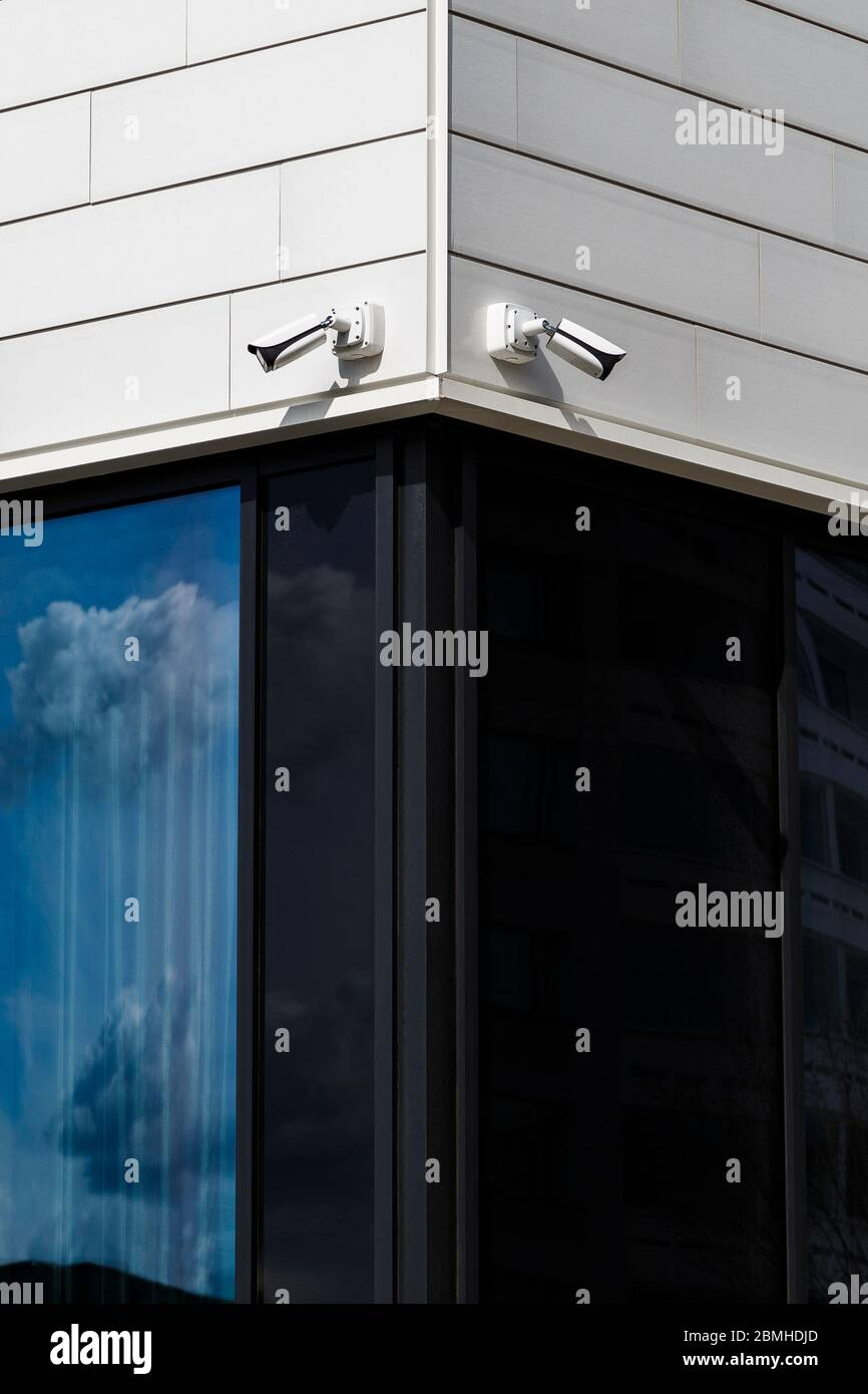 Two CCTV security surveillance cameras mounted on a corner of a modern office building. Stock Photo