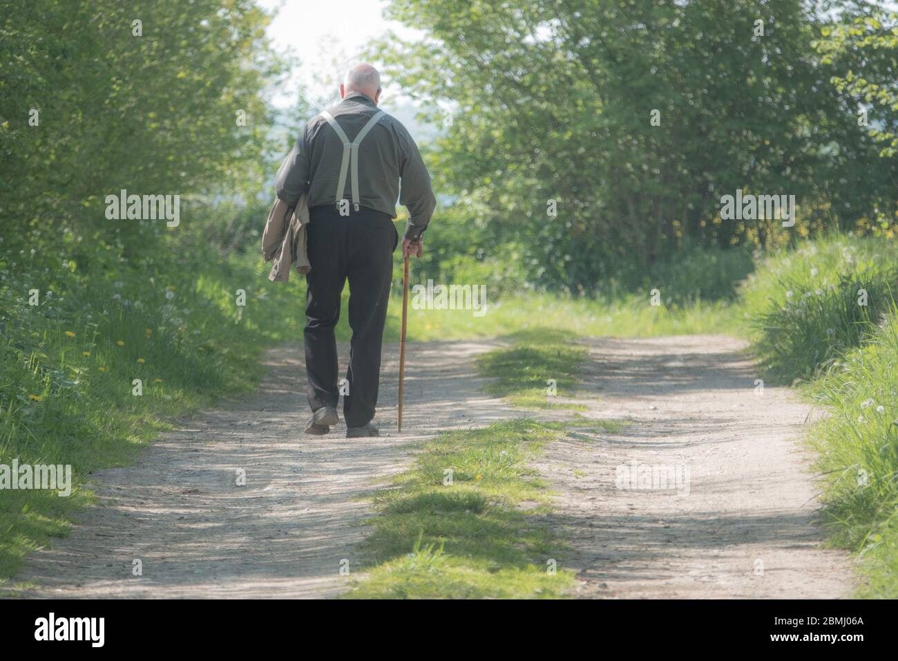 an old man walks along a country lane on a walking stick Stock Photo