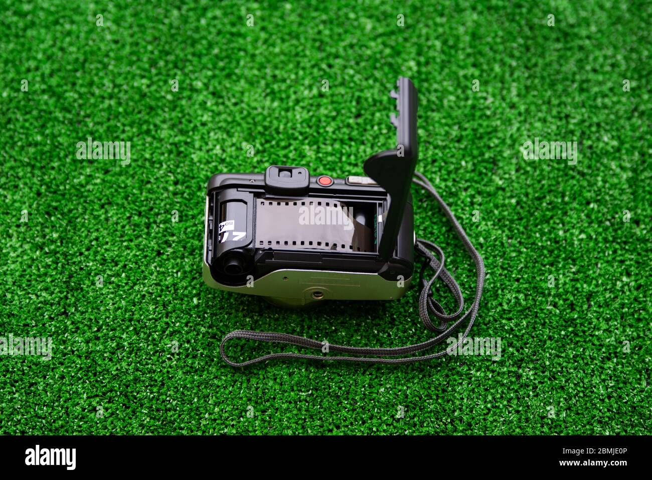Old analog camera back door and photo film on grass background. Analog photography. Stock Photo
