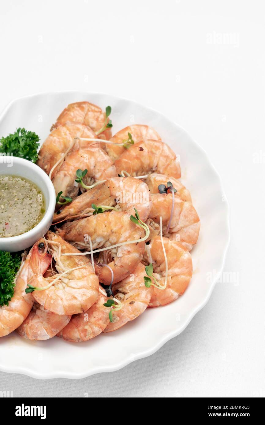 fresh boiled prawns with zesty citrus dipping sauce on white background Stock Photo