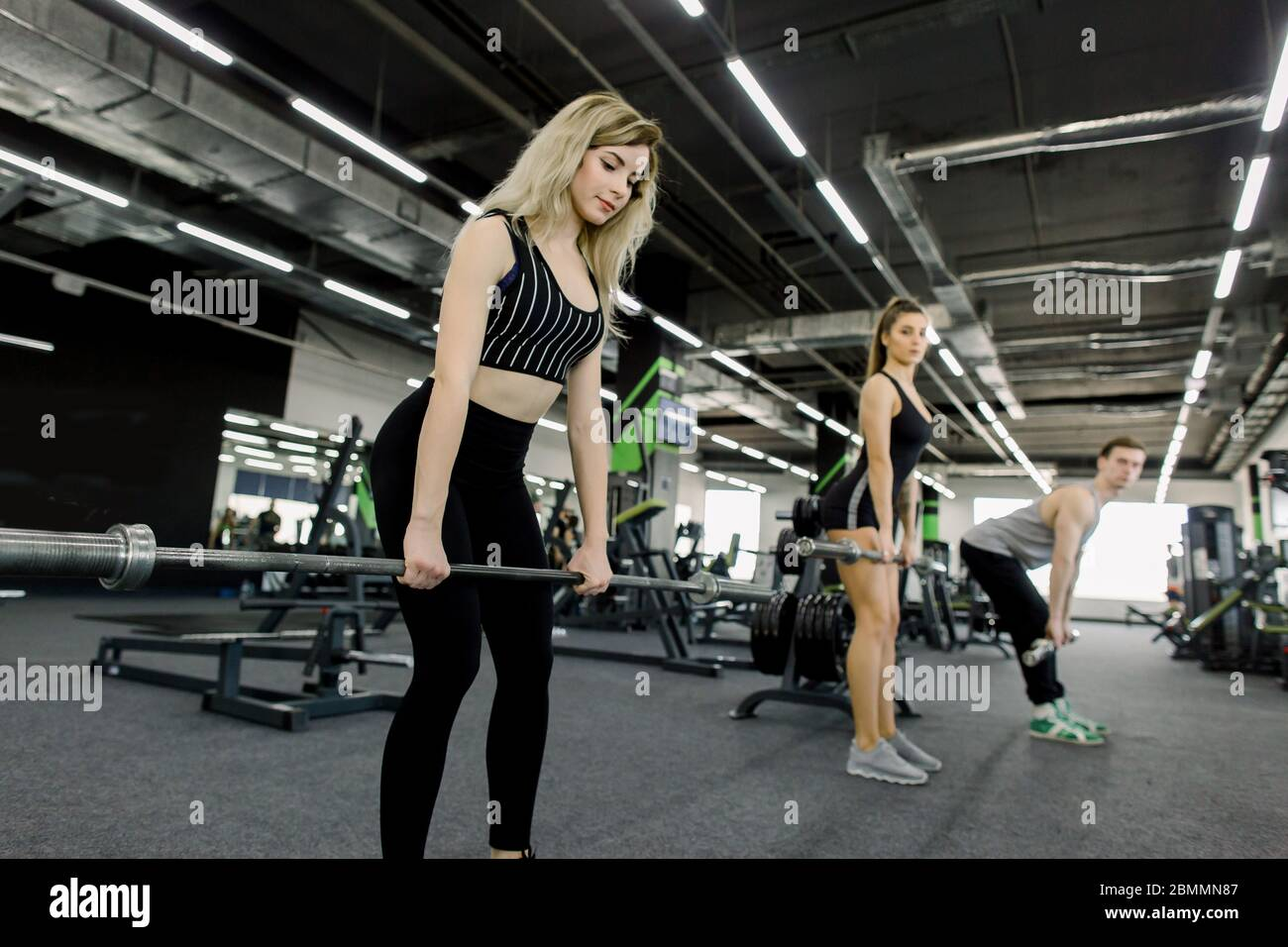Close-up - Sporty Athletic Man and Women Training With Barbells. Cross fit  training. Young people During Workout in Gym. Strength Training Stock Photo  - Alamy