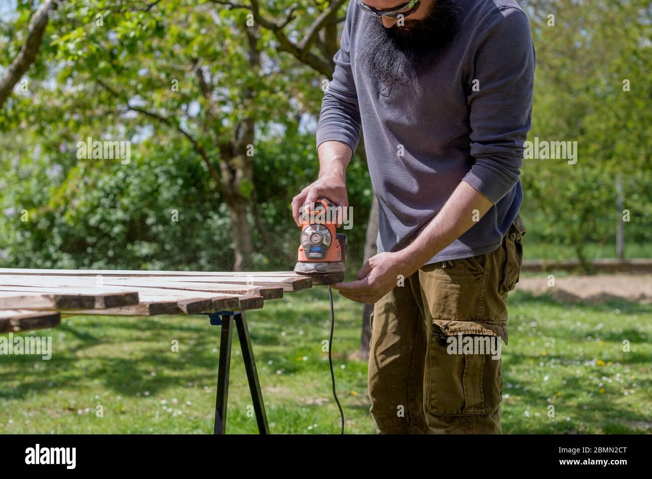 Mid adult caucasian man in the garden sanding wooden planks. DIY home improvement, restoration, carpentry concept. Stock Photo