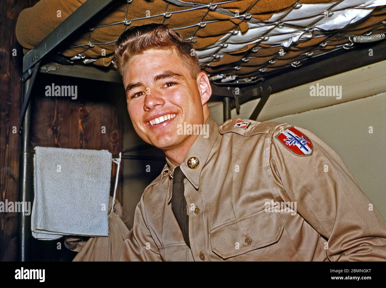 A US Army soldier stationed in Germany in the mid-1950s – a member of the 160th Signal Group is pictured on a bunk bed at the Panzer Kaserne (PK) headquarters, in Böblingen. In uniform, his hair has a quiff, a style popular in that era. From 1955 the 160th Signal Group provided communications throughout Germany under the US 7th (Seventh) Army during the Post-war era from an HQ at Panzer Kaserne (PK), in Böblingen (Boeblingen) near Stuttgart. The US 7th Army's HQ was at nearby Patch Barracks. Stock Photo