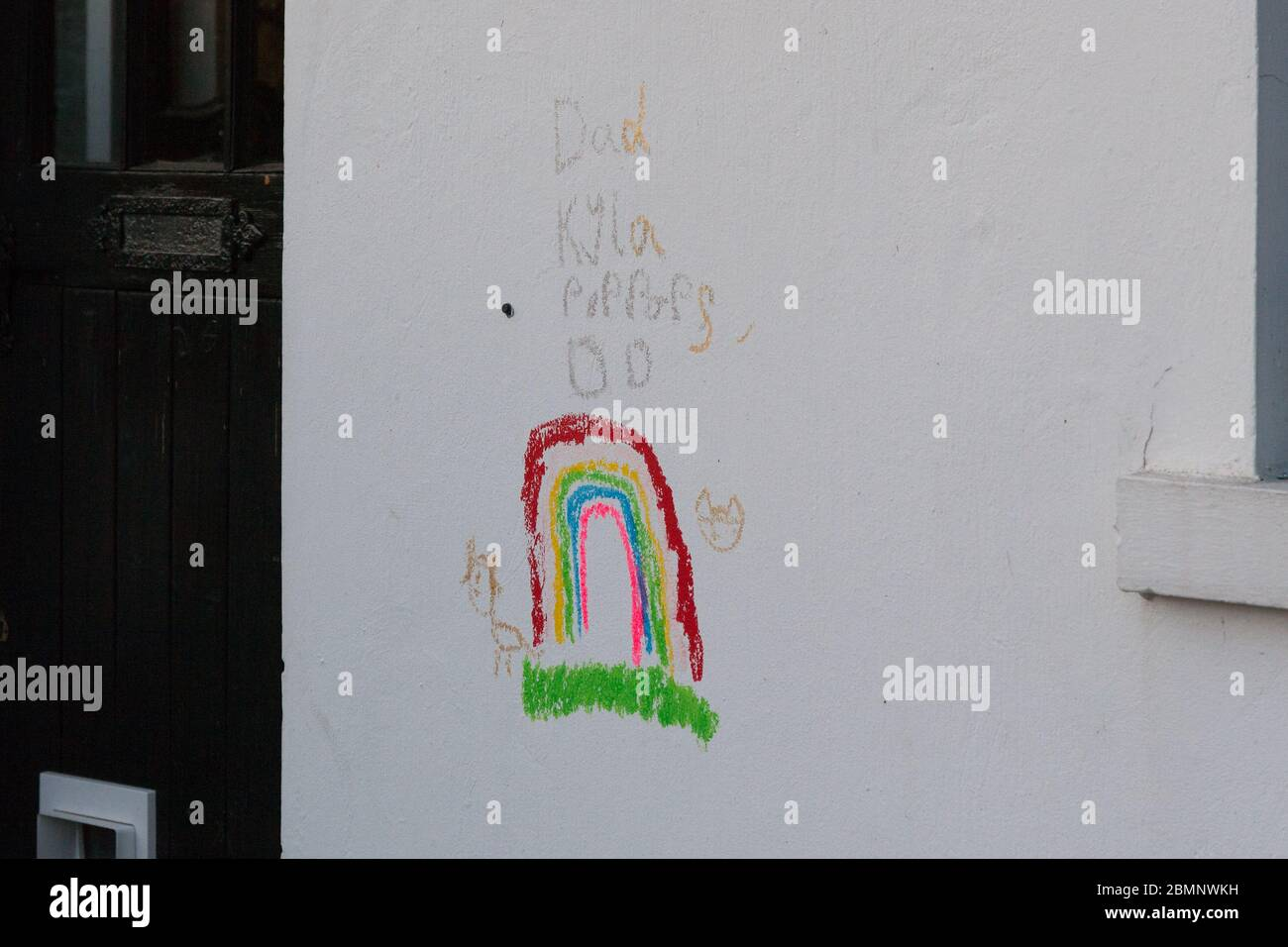 Huddersfield, UK - May 4 2020: A child's drawing of a rainbow in crayon on the side of a house in West Yorkshire. Stock Photo