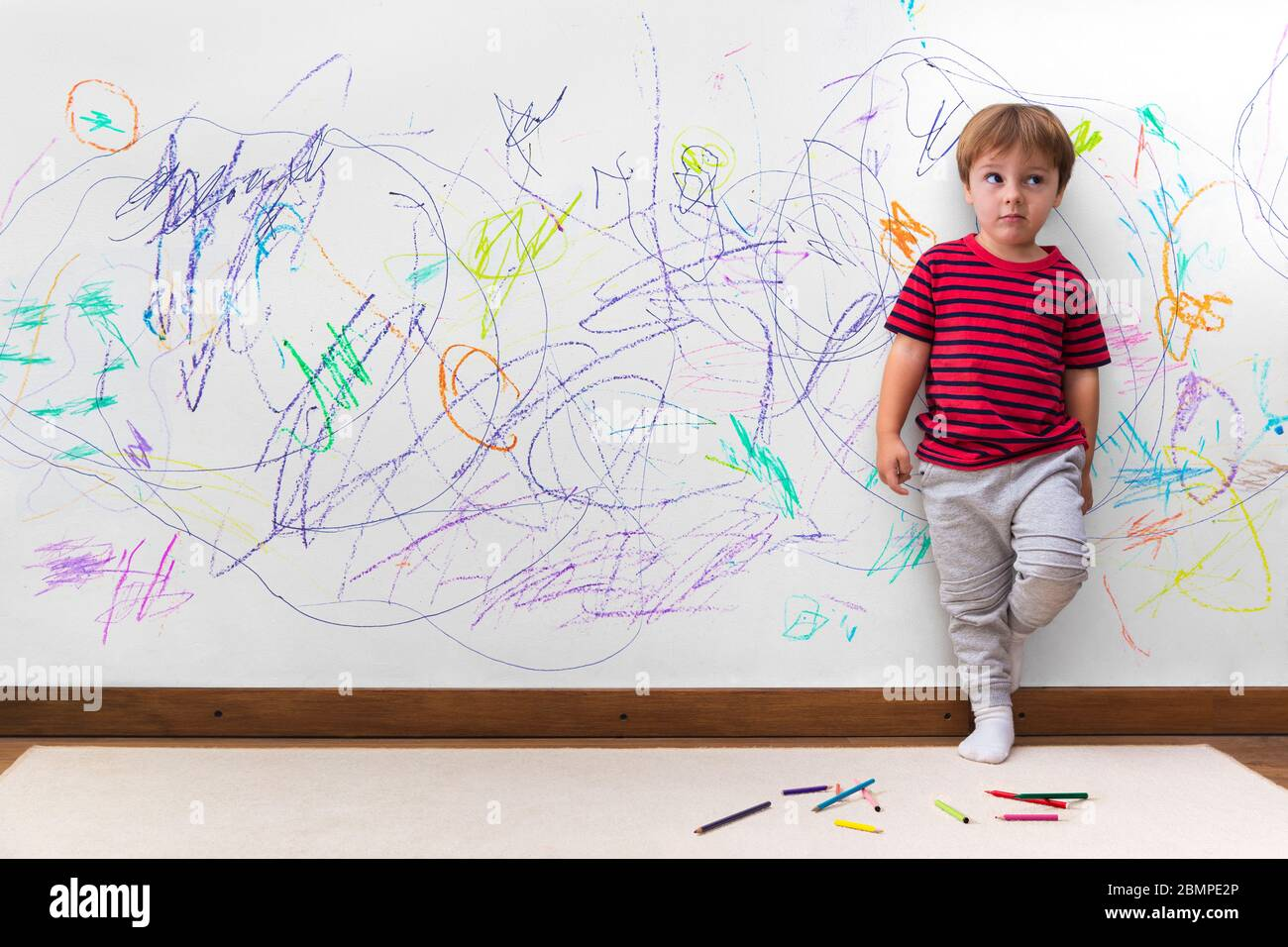 Child mischief. Boy with a distracted face because he drew the entire wall. Little boy leaning against the white wall where he made many drawings Stock Photo