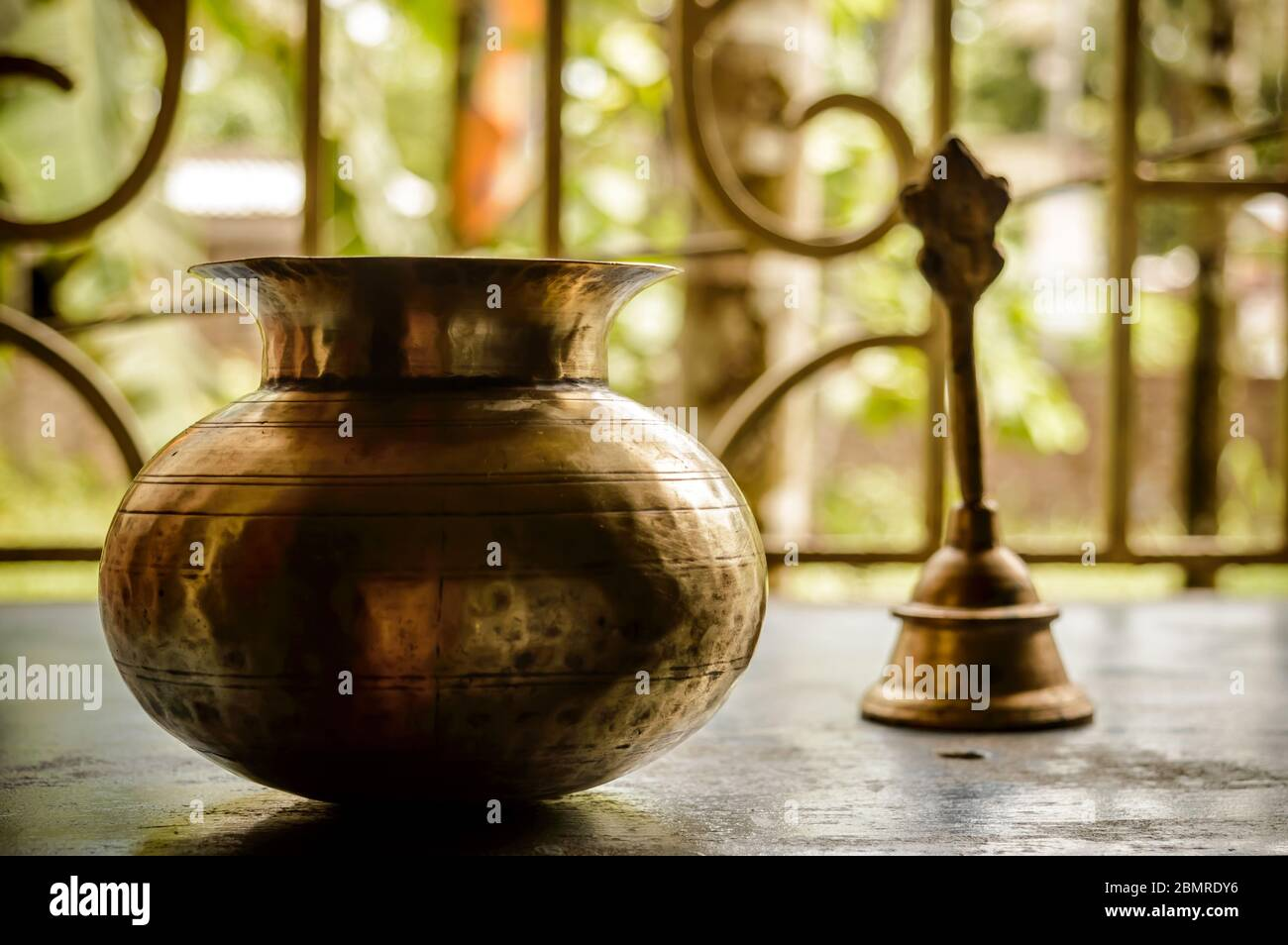 Close up Still Life of antique Holi water pot and bell on rustic floor. Faith, Tradition, Spirituality, Prayer, symbols of peace and Religious Themes. Stock Photo