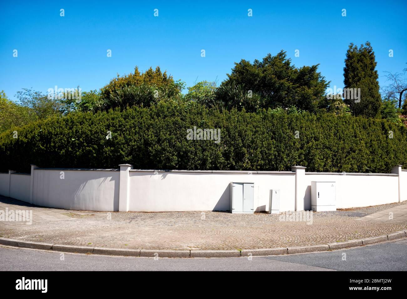 Sichtschutz vor neugierigen Blicken. Hecken und Mauern als Grundstuecksgrenzen. Stock Photo