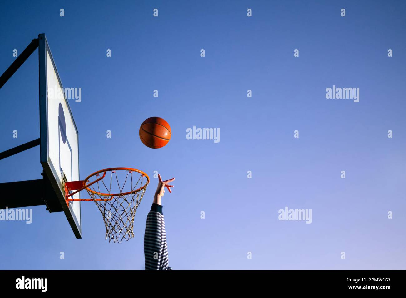 Street basketball ball player throwing ball into the hoop. Close up of hand, orange ball above the hoop net with blue sky in the background. Concept o Stock Photo