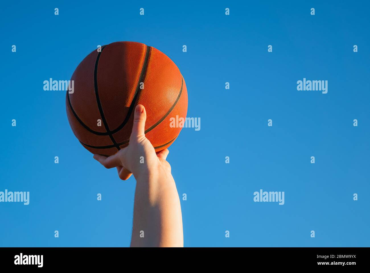 Close up of professional basketball player holding a ball in the hand. Street basketball athlete with a ball and blue sky in the background Stock Photo