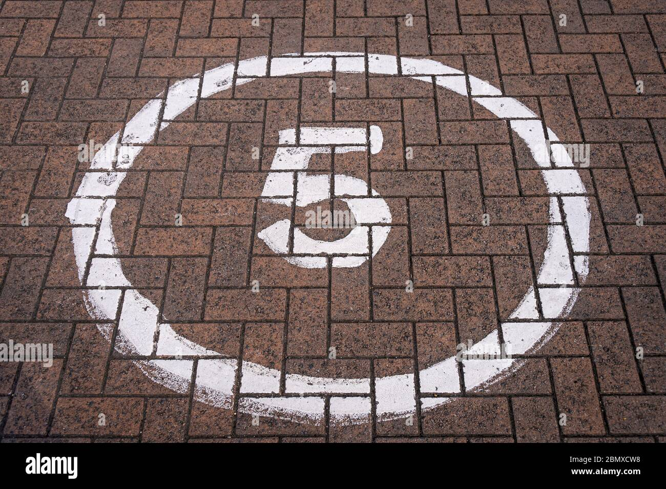 5 mph sign in a circle painted on a block road Stock Photo