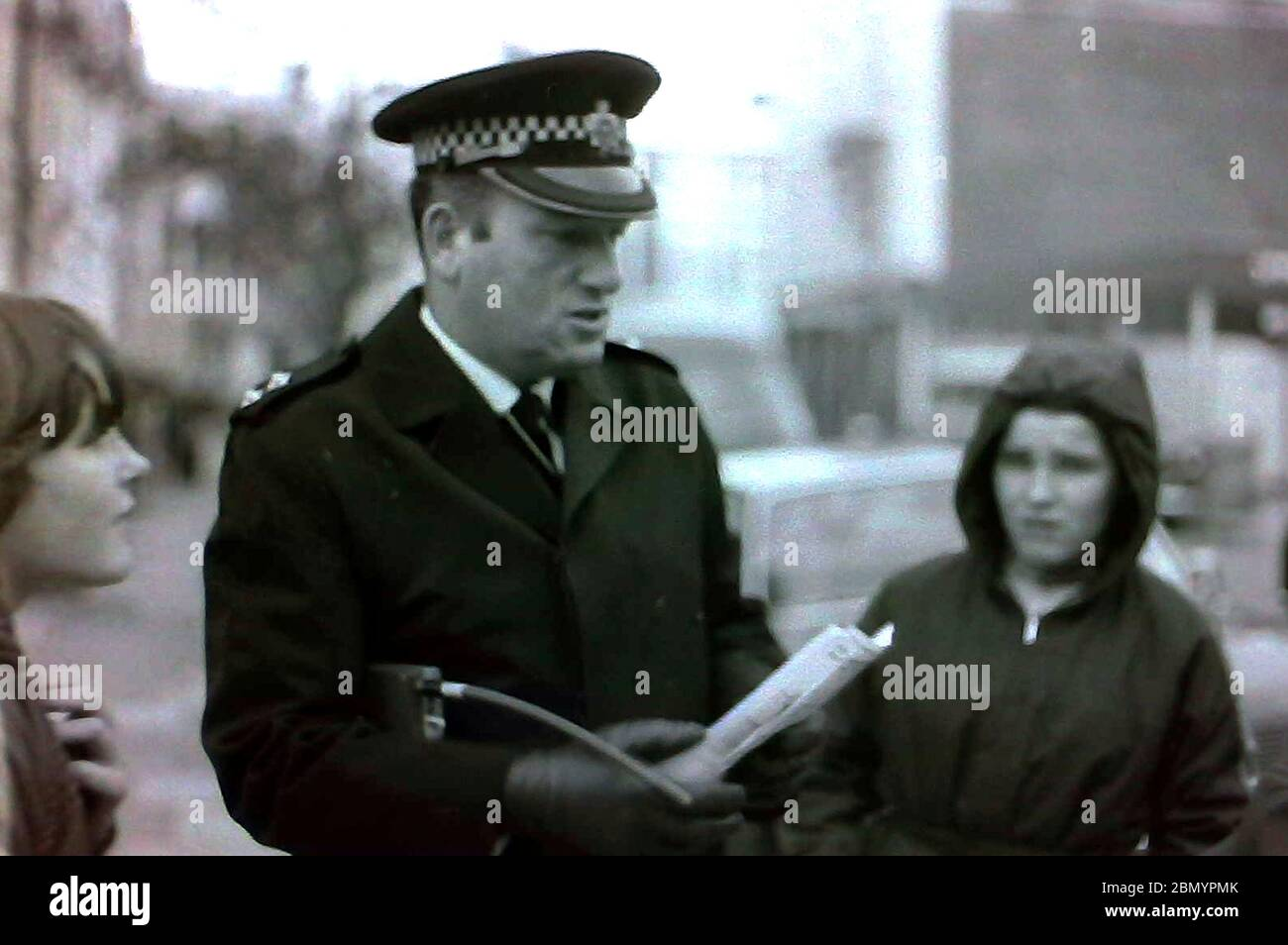 A senior police officer with a radio under his arm talks to young people in the street in Manchester, uk, in the 1970's Stock Photo