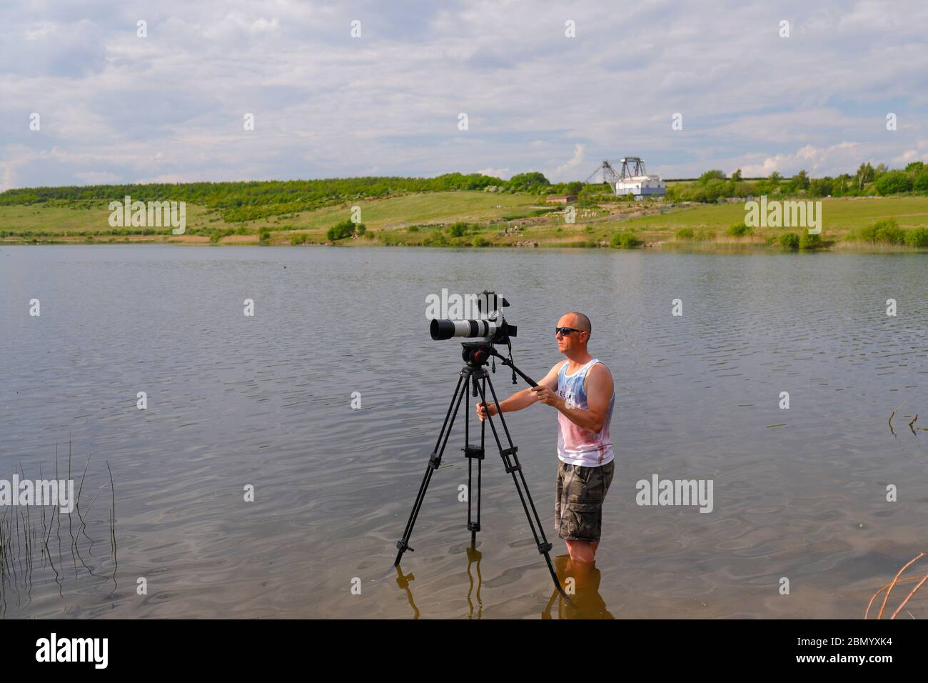 A photographer standing in shallow water, to get the angle that wasn't possible from the edge of the lake at RSPB St Aidan's Stock Photo