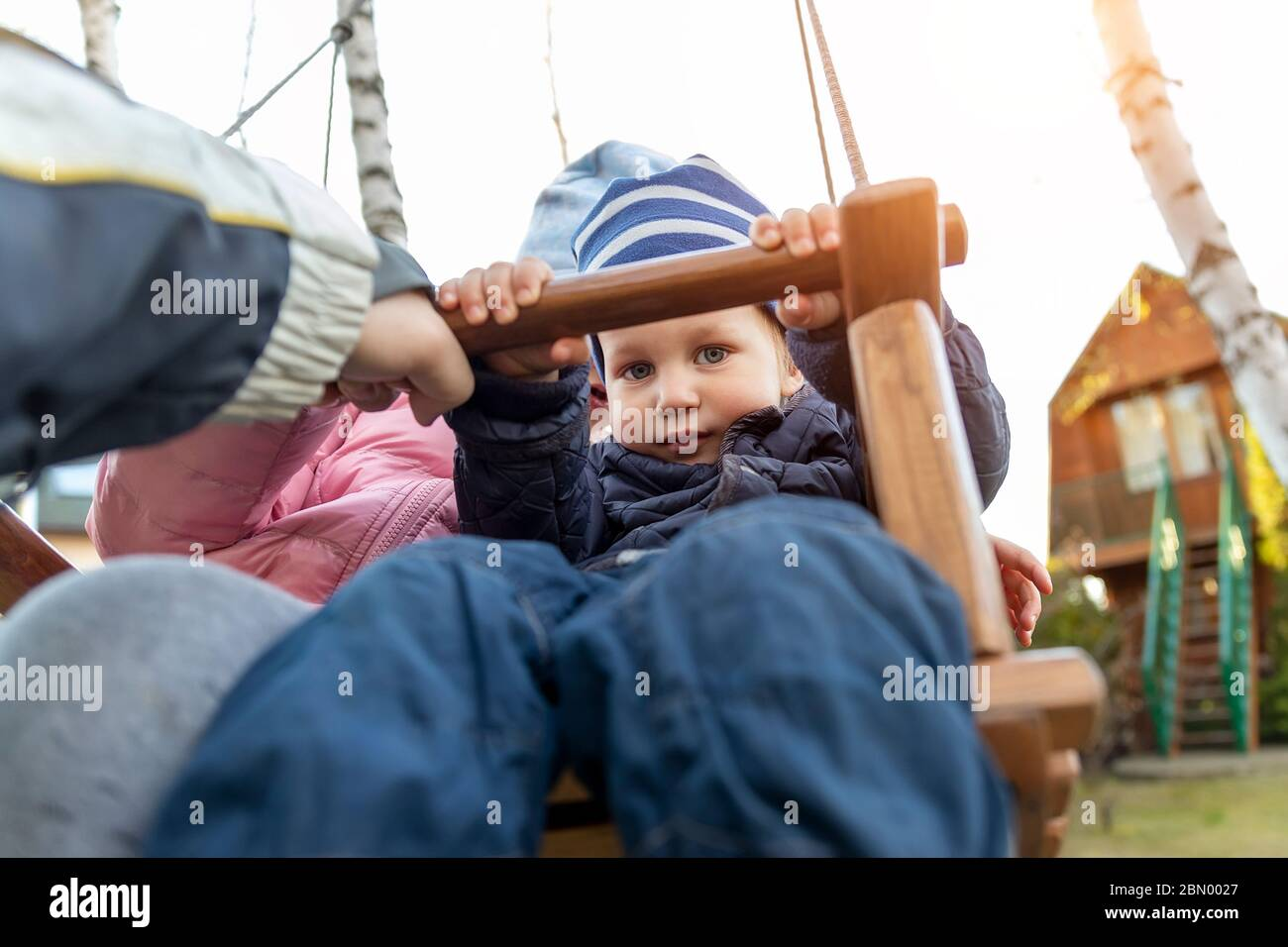 Two cute adorable playful caucasian siblings boy girl child enjoy having fun swinging wooden swing at backyard together with father. Little toddler Stock Photo