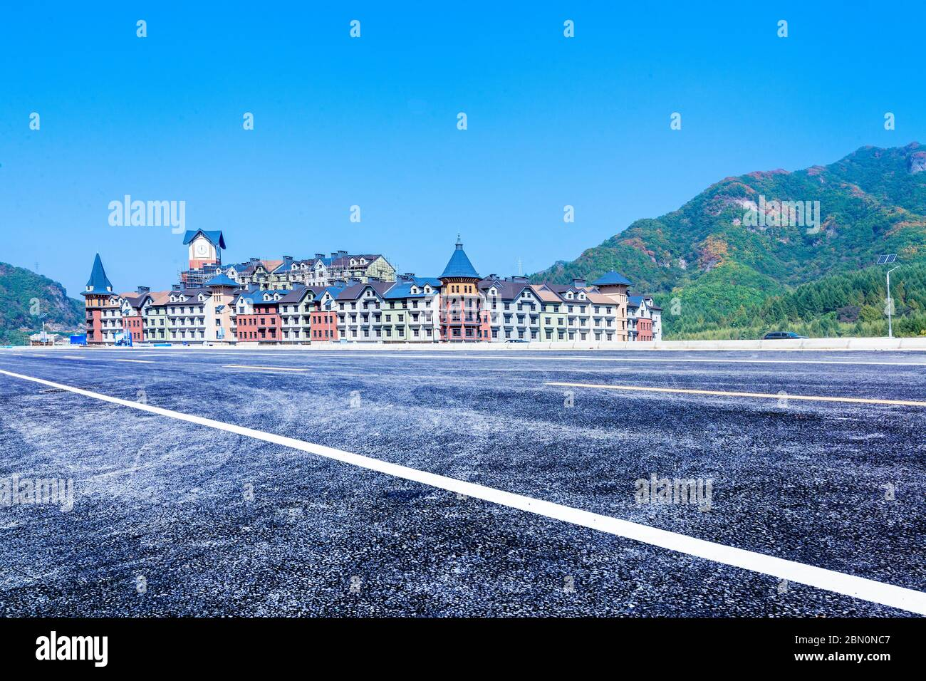 The empty car-free highway and the European-style building castle, in the distance are green mountains. Stock Photo