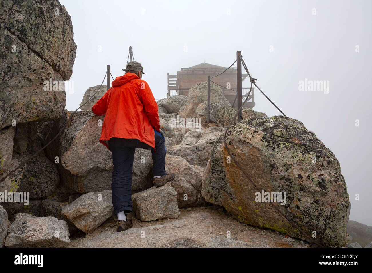 WY04219-00...WYOMING - Hiker approaching the Black Mountain Lookout on a foggy day in the Bighorn National Forest. Stock Photo