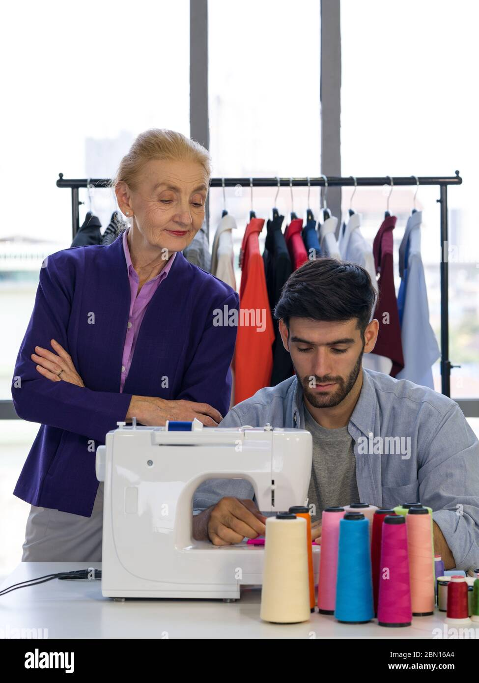 Senior Fashion Designers Closely Control The New Designers In Their Work That Requires Electric Sewing Machines Man And Woman Working In Home Base Cl Stock Photo 357142076 Alamy