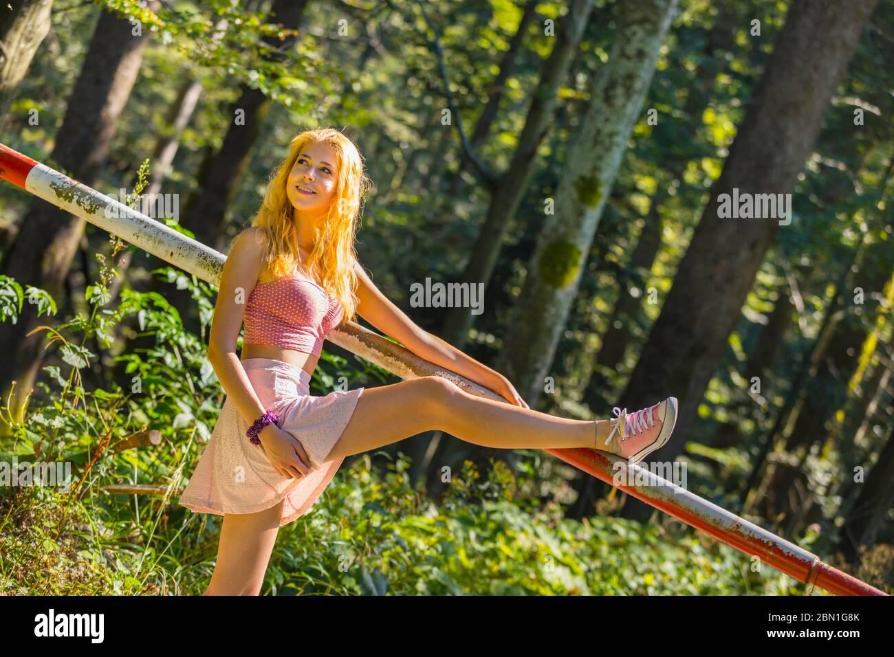 Teengirl blonde joyful in nature raising leg high on offlimit off-limit pretending pretend to cross across above transpass looking back aside away Stock Photo